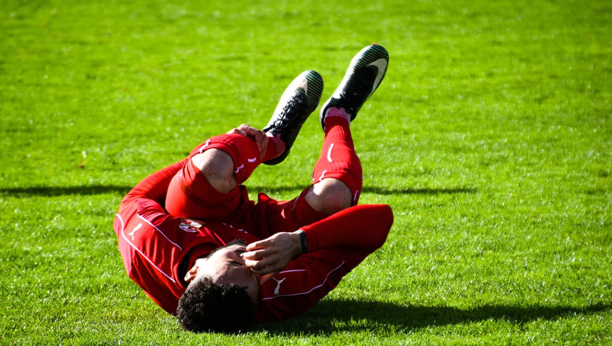 Soccer player laying in pain due injury or torn muscle